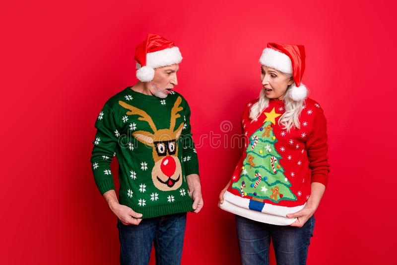 Photo of two astonished excited people grey white haired husband wife showing funny cartoon pictures on reindeer stock photography