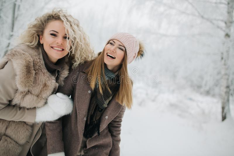 Photo of two blonde women on walk in winter forest. At day stock photography