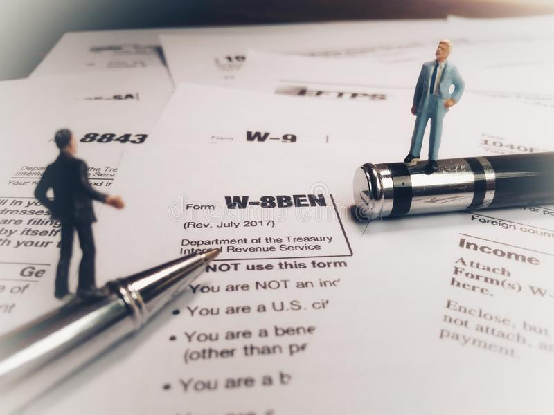 Two businessman discussion about usa tax form, w-8ben, certificate of foreign status of beneficial owner for united states tax wit. Photo two businessman stock images