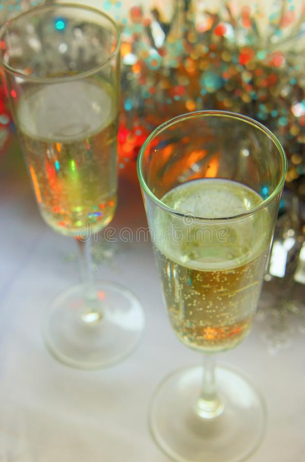 Photo of two champagner glasses on festive table with christmas ornaments and bokeh background.  royalty free stock image