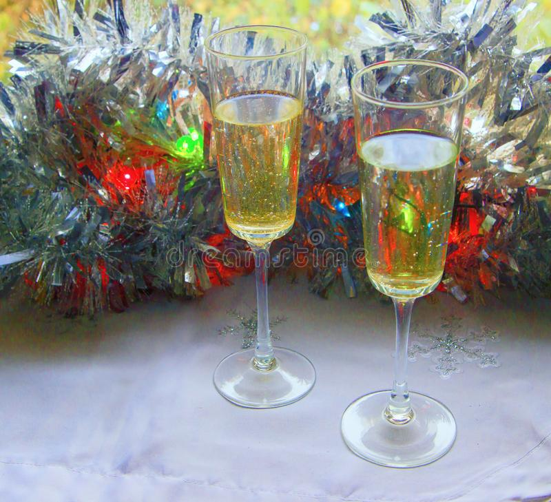 Photo of two champagner glasses on festive table with christmas ornaments and bokeh background.  royalty free stock photo