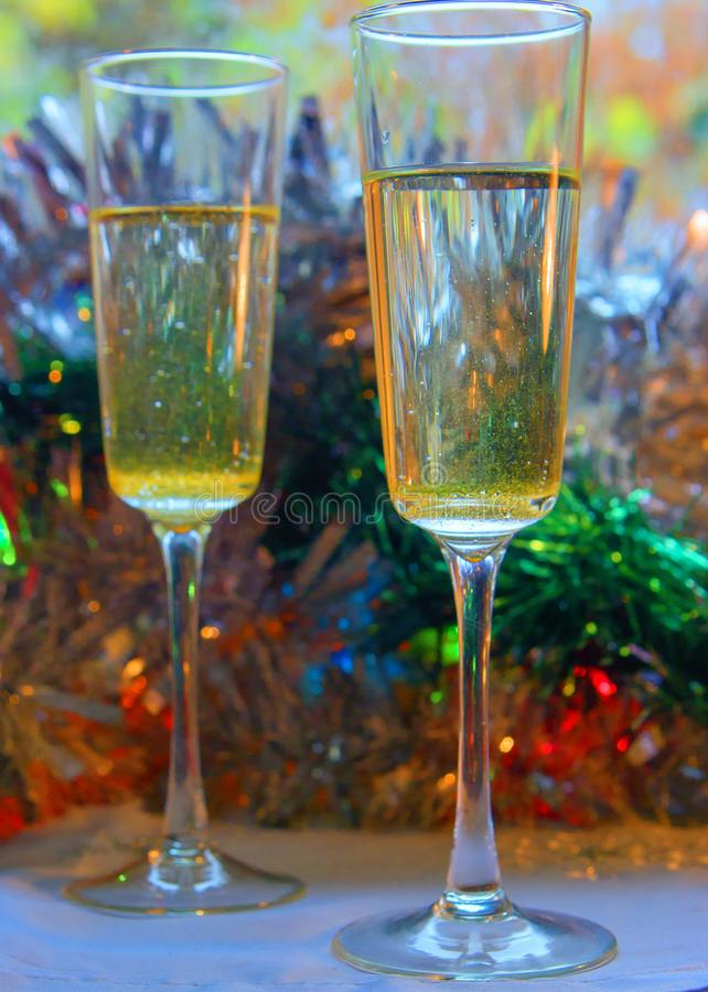 Photo of two champagner glasses on festive table with christmas ornaments and bokeh background.  royalty free stock photos