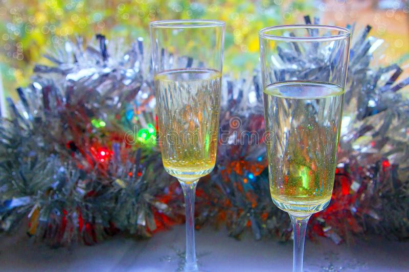 Photo of two champagner glasses on festive table with christmas ornaments and bokeh background.  stock photography