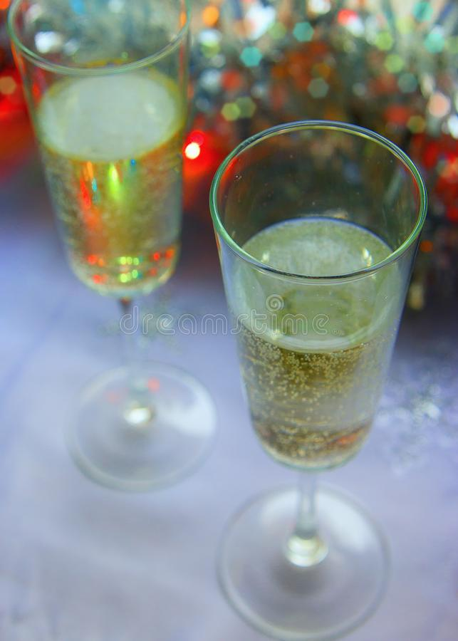 Photo of two champagner glasses on festive table with christmas ornaments and bokeh background.  royalty free stock photography