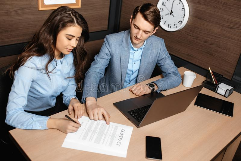 Photo of two colleagues working together with laptop and business documents in modern office. Business woman and man royalty free stock photo