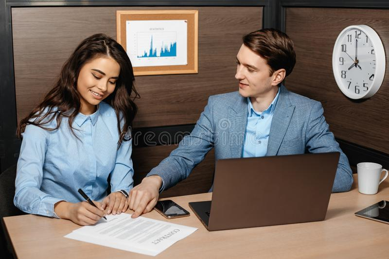 Photo of two colleagues working together with laptop and business documents in modern office. Business woman and man stock photos