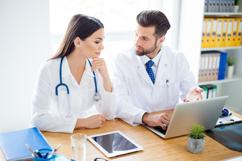 Photo of two doctors together discussing new way of treatment while having a meeting at office stock photo