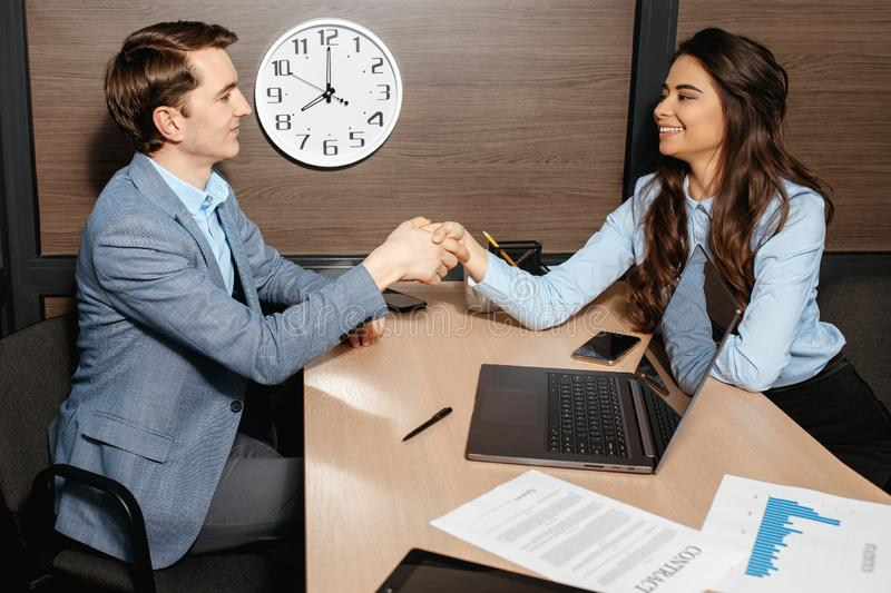 Photo of two happy business colleagues press hands each other in modern office. Celebrating business success. stock photos