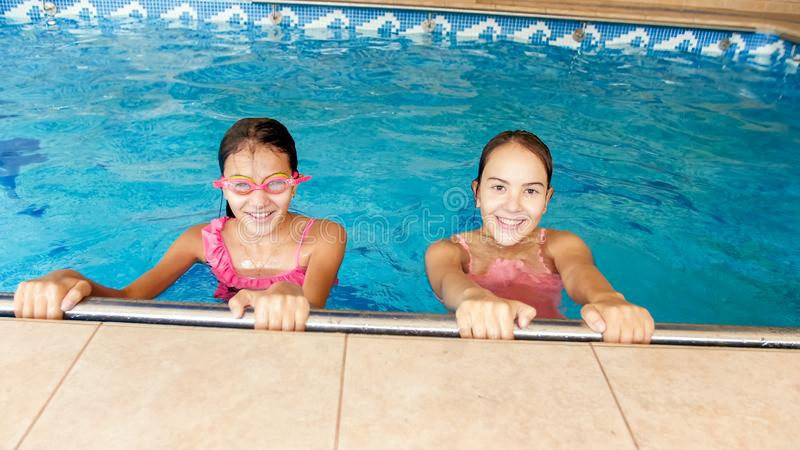 Portrait of two happy girls friends posing in indoors swimming pool royalty free stock photo