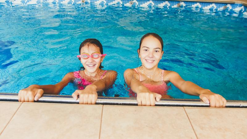 Portrait of two happy girls friends posing in indoors swimming pool royalty free stock photos