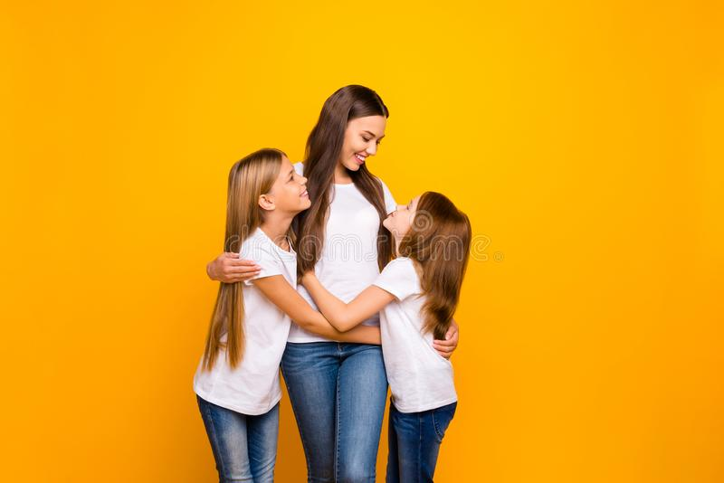 Photo of two little ladies hugging with pretty mommy wear casual outfit isolated yellow background royalty free stock images