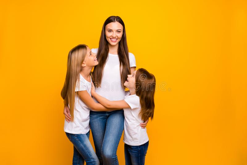 Photo of two little ladies with lovely babysitter wear casual outfit isolated yellow background royalty free stock images