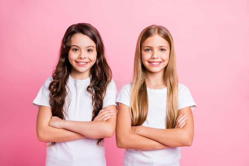Photo of two nice good friendly girls with their hands folded staring at camera while isolated with pink background royalty free stock image
