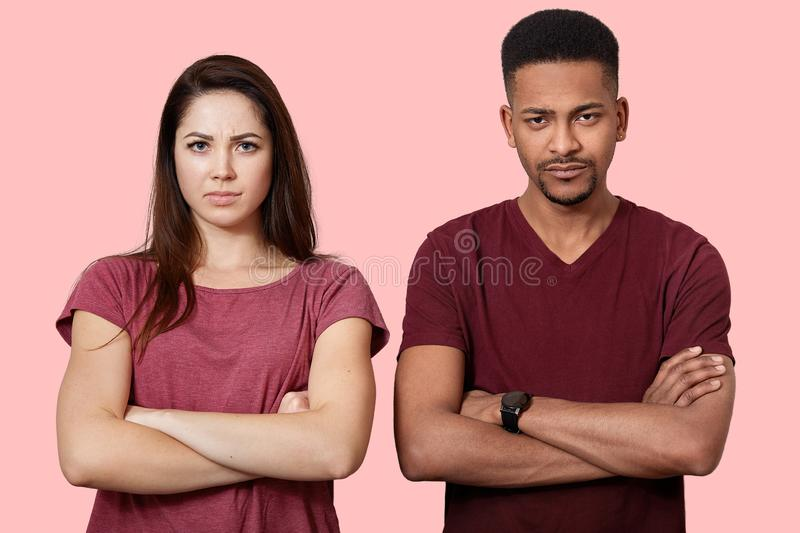 Photo of two offended young people in love, keep hands crossed, have crisis in their family, pose at pink studio wall, being stock photography