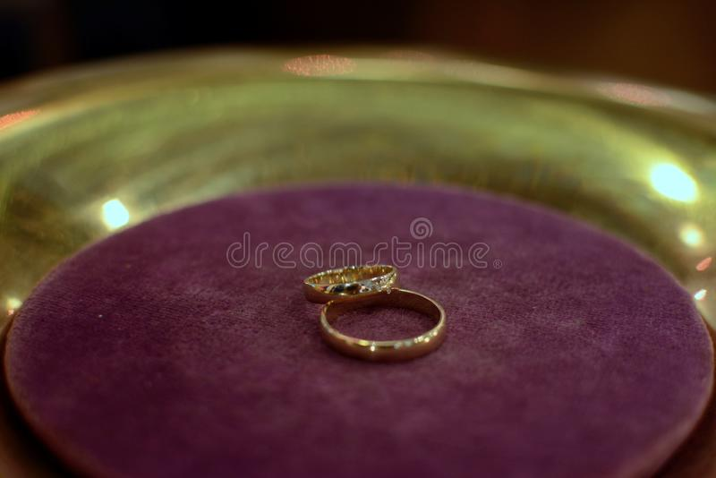 Wedding rings of for future married couple on purple velvet royalty free stock photos