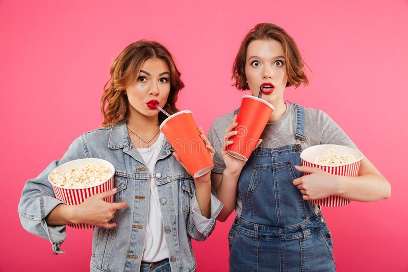 Shocked women friends eating popcorn watch film. Photo of two shocked women friends standing isolated over pink background. Looking camera eating popcorn watch stock photography