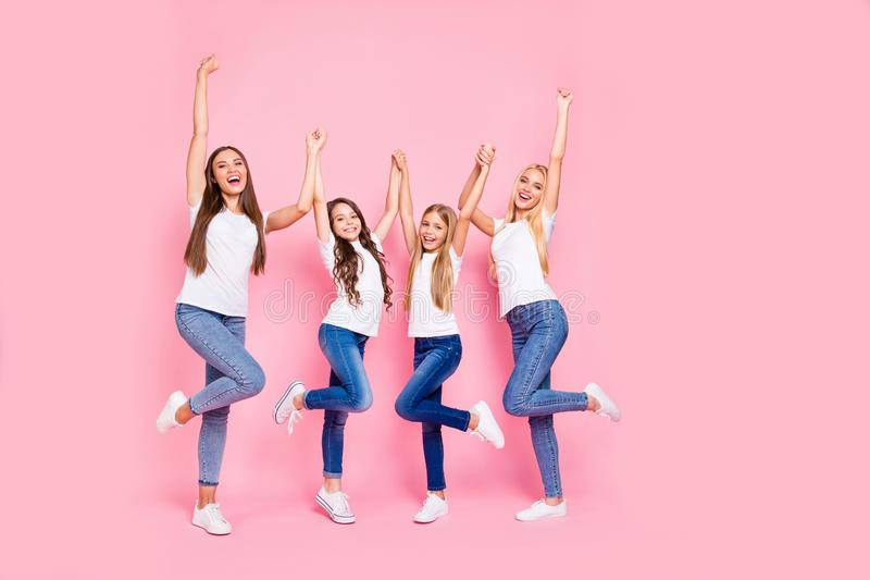 Photo of two small and two students ladies raising arms up wear casual outfit isolated pink background royalty free stock image