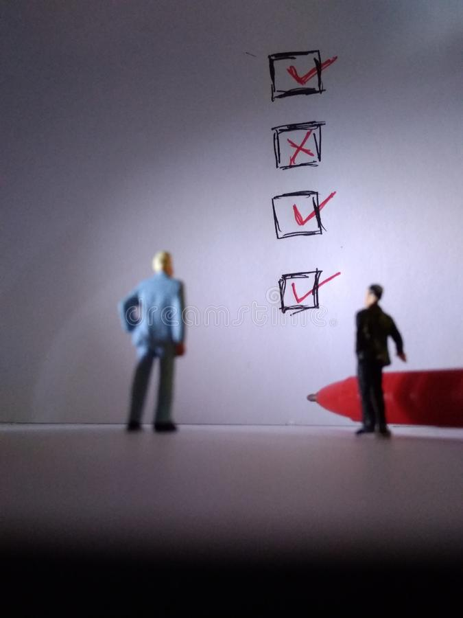 Two standing businessman mini figure toys, meeting, check list stock images