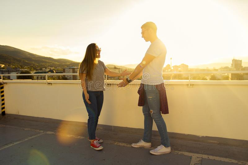 YOUNG BEST FRIENDS IS TALKING ON THE TERRACE  ON THE TOP OF THE royalty free stock image