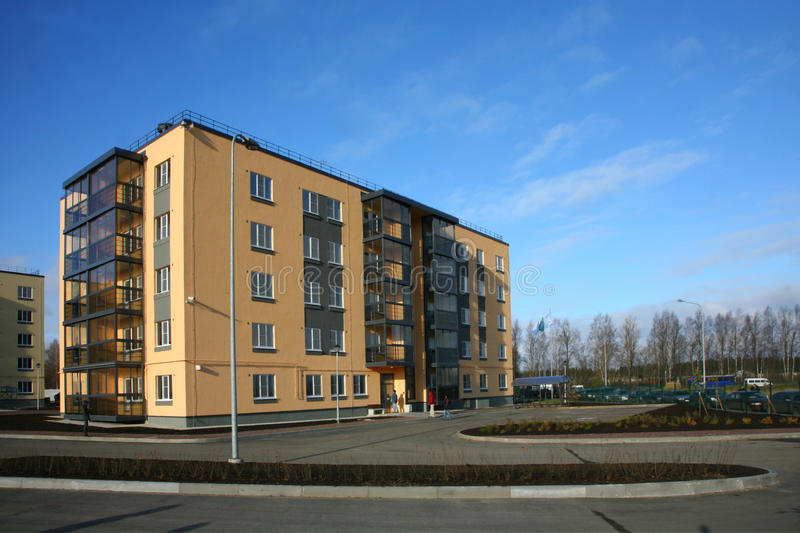 Photo typical apartment block of 5-storey yellow-gray-brown house. With a glazed hinged balconies and paved local area. Against the blue spring sky with rare stock image