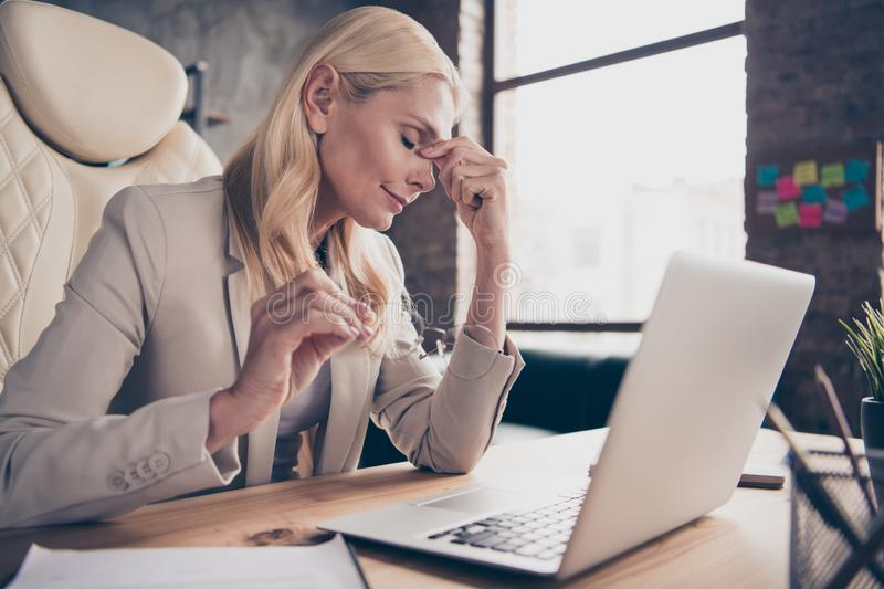 Photo of unhappy diseased blonde haired business woman suffering from head ache hurting having to have some rest because royalty free stock photography