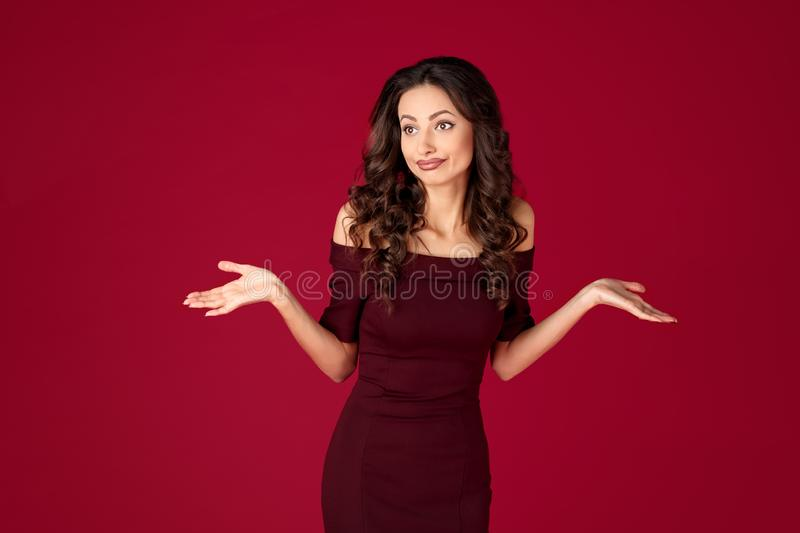Photo of unhappy young woman in maroon dress over red background. Photo of unhappy young woman in maroon dress over red background royalty free stock images