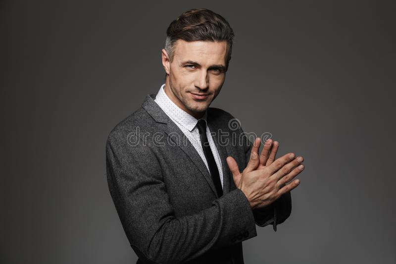 Photo of unshaved successful man 30s wearing office suit and black tie smiling on camera holding hands together, isolated over gr. Photo of unshaved successful stock photography