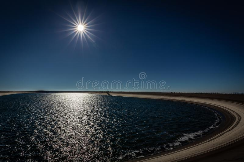 Photo of the upper water reservoire with sun and dark blue sky stock image