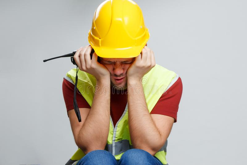 Photo of upset worker in yellow helmet with walkie talkie. stock images