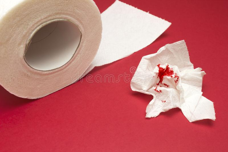 A photo of used bloody toilet paper and a tiolet paper roll. Blood drops and traces. Hemorrhoids, constipation treatment health pr. A photo of used bloody toilet stock photos