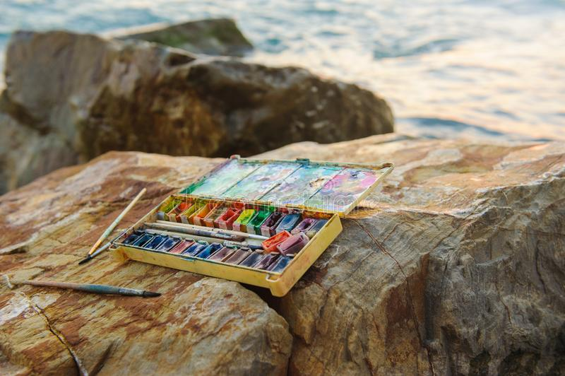 Photo used water-color paint-box, paint brushon ,brushes on stones near the sea shore. Photo vertical Used water-color paint-box, paint brushon ,brushes on stock photos