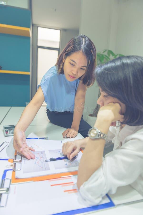 Photo verticale des hommes d'affaires asiatiques discuter au sujet du document financier photographie stock