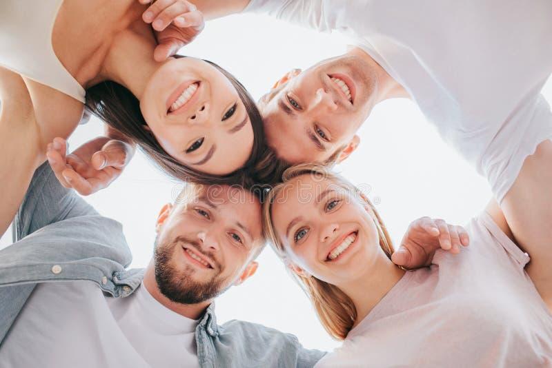 Photo verticale des jeunes hommes heureux et positifs et des femmes se tenant près de l'un l'autre et regardant vers le bas sur l images libres de droits