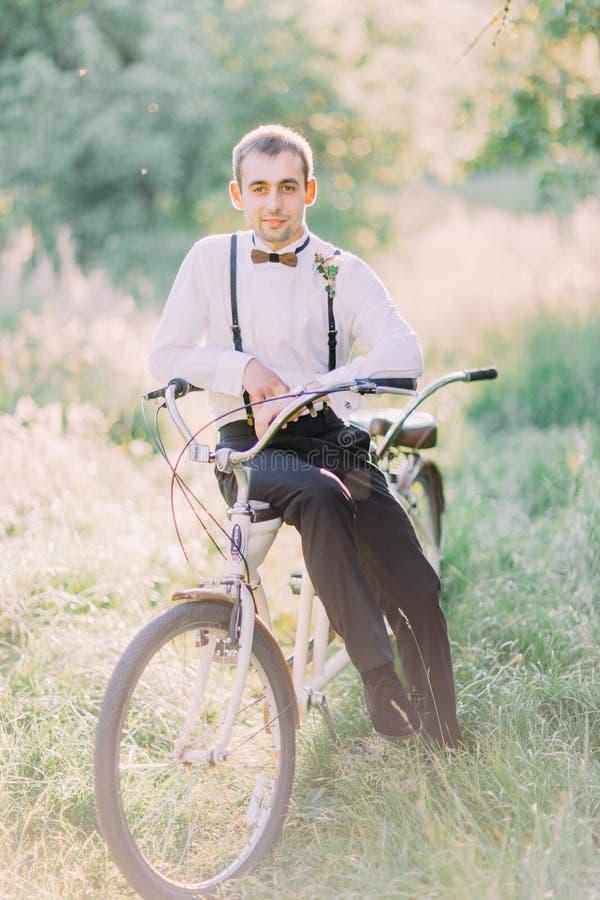 Photo verticale du meilleur homme dans le costume noir se reposant sur la bicyclette au fond de la forêt ensoleillée photographie stock libre de droits
