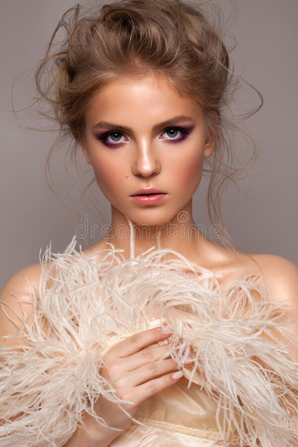 Photo of a very beautiful natural blond model with professional purple makeup, perfect skin and ostrich feather boa. Portrait of a very beautiful natural blond stock photo