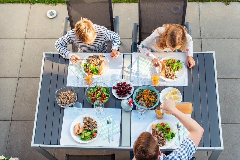 View from above of happy family eating healthy dinner on terrace royalty free stock photos