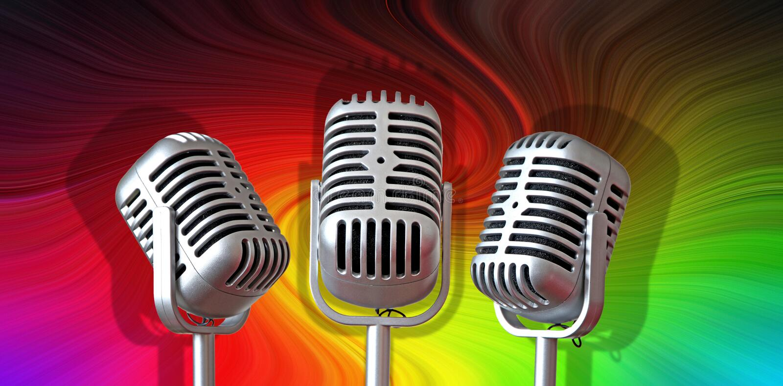 Old vintage mics microphones recording sound music singing studio stage. Photo of vintage trio microphones set against a colourful swirling background ideal for royalty free stock photography