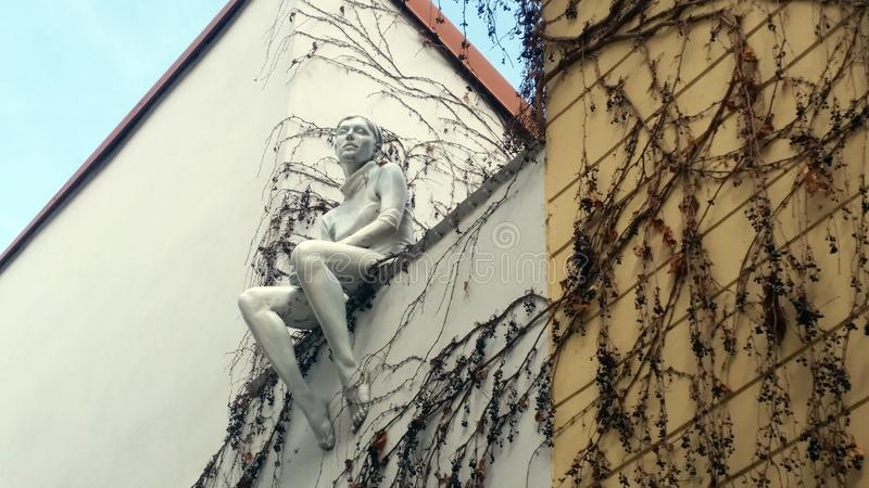 Statue-Sitting woman in one of Prague streets royalty free stock photo