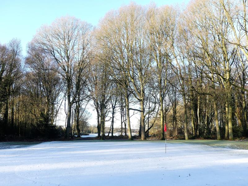 Snow covered golf course with red flag, Chorleywood Common stock image