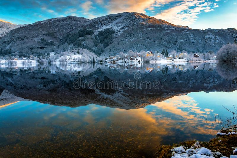 Winter Landscape with Snowy Mountains, Colorful Clouds, Lake Reflection at Sunset royalty free stock image