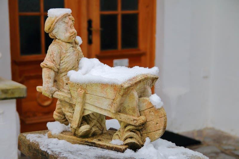 Funny boy figurine with a wheelbarrow stock photography