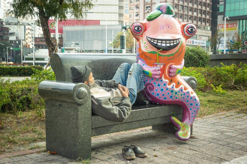 Tainan/Taiwan-13.03.2018:The funny statue and sleeping homeless man stock photo