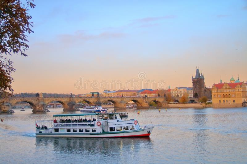 Pleasure boat on the Vltava River in Prague against the backdrop of Charles Bridge at sunset royalty free stock images