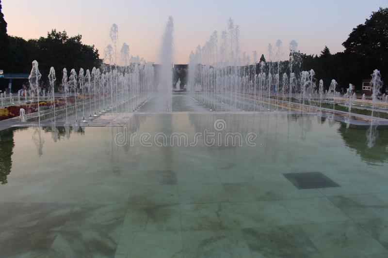 Fountains in front of the National Palace of Culture in the evening in Sofia August summer heat and cool near fountain frame. This photo  was taken in Sofia royalty free stock images
