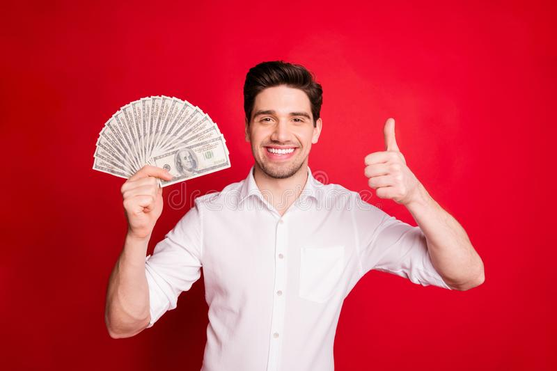 Photo of wealthy fashionable trendy brunet man showing you result of his work while isolated with red background. Photo of wealthy fashionable trendy, brunet man royalty free stock photo