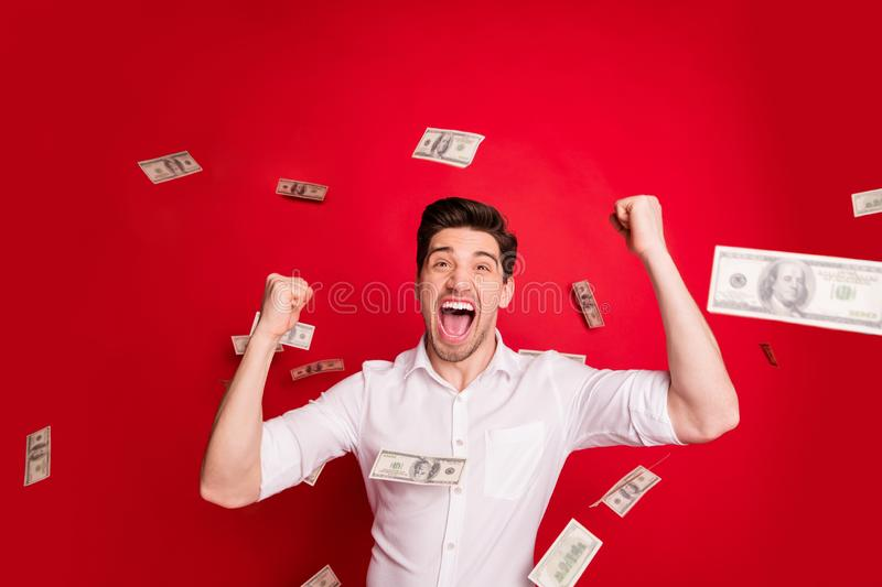 Photo of wealthy rejoicing overjoyed man standing in rain of dollar banknotes while isolated with red background. Photo of wealthy rejoicing overjoyed, man royalty free stock images