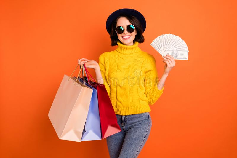 Photo of wealthy rich toothily smiling lady wearing jeans denim yellow pullover having just purchased packages in. Photo of wealthy rich toothily smiling, lady royalty free stock image