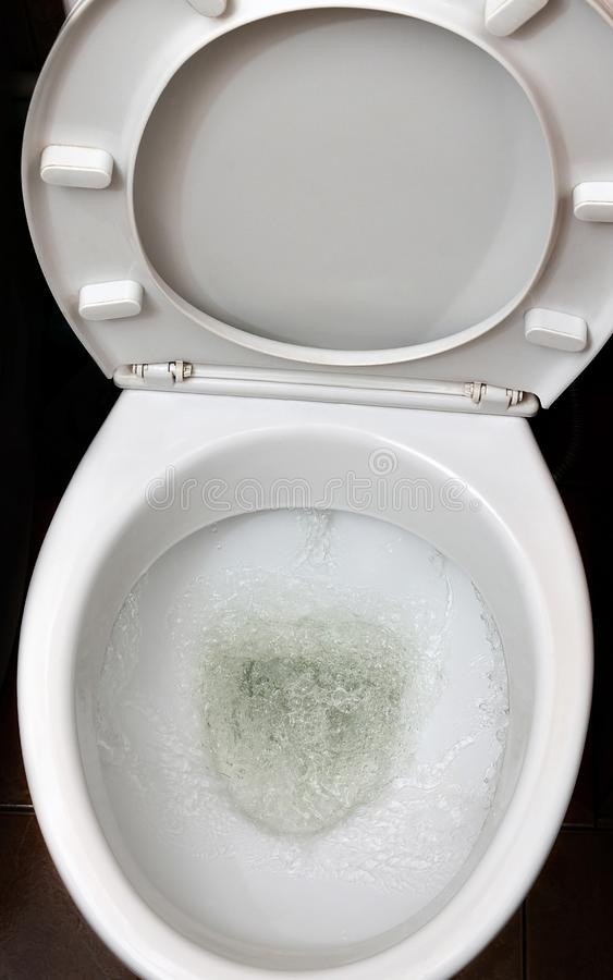 A photo of a white ceramic toilet bowl in the process of washing it off. Ceramic sanitary ware for correcting the need with an au. Tomatic flushing device stock photo