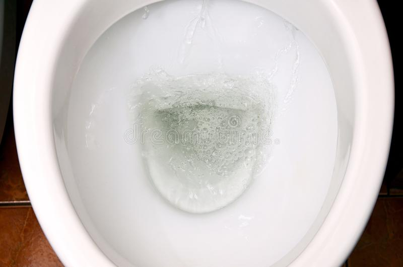 A photo of a white ceramic toilet bowl in the process of washing it off. Ceramic sanitary ware for correcting the need with an au. Tomatic flushing device stock photos