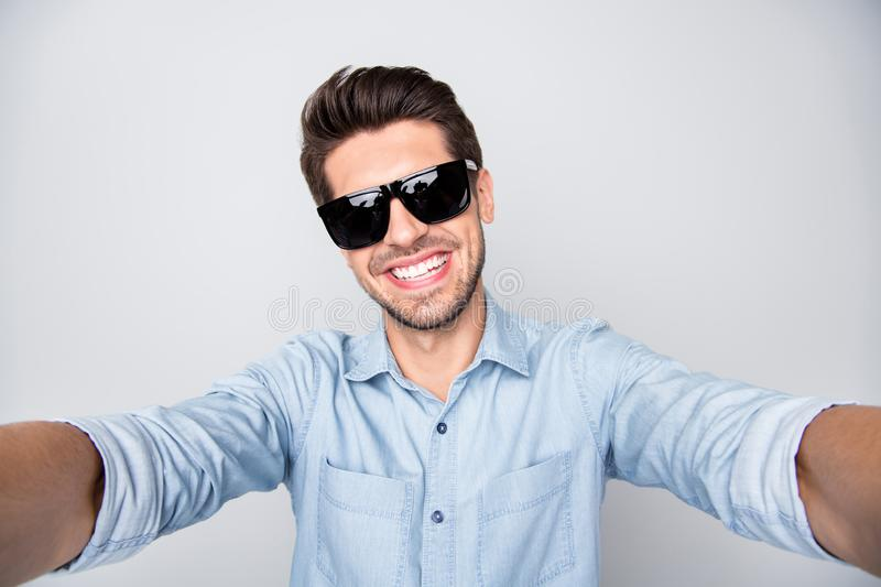 Photo of white cheerful attractive handsome man taking selfie showing his teeth in smile wearing spectacles isolated royalty free stock photos